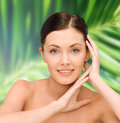 Smiling young woman with bare shoulders beauty people and health concept over palm tree leaves background Stock Photo