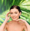 Smiling young woman with bare shoulders beauty people and health concept over palm tree leaves background Stock Photos