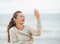 Smiling young woman on beach taking self photo using cell phone in sweater Royalty Free Stock Photos
