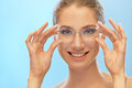 Smiling young woman beautiful holds her hands glasses on blue background Royalty Free Stock Photo