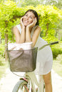 Smiling young woman with bicycle in the park at beautiful spring day Stock Images