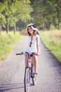Smiling young woman biking on a country road Royalty Free Stock Photo