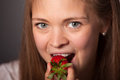 Smiling young woman biting a fresh strawberry close up pretty fruit while looking at the camera on gray background Royalty Free Stock Photos