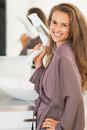 Smiling young woman with blow dryer in bathroom Royalty Free Stock Photo