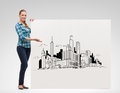 Smiling young woman with board and city drawing happiness advertising people concept pointing hand to white Royalty Free Stock Photos