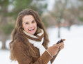 Smiling young woman with cell phone in winter outdoors Royalty Free Stock Photo