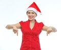 Smiling young woman in Christmas hat pointing down Stock Images