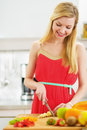 Smiling young woman cutting fresh fruits salad Royalty Free Stock Photo