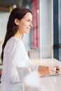Smiling young woman drinking coffee at cafe leisure drinks people and lifestyle concept Royalty Free Stock Image