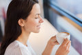 Smiling young woman drinking coffee at cafe leisure drinks people and lifestyle concept close up of Stock Photos