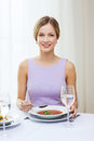 Smiling young woman eating appetizer at restaurant Royalty Free Stock Photo