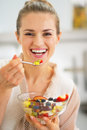 Smiling young woman eating fresh fruit salad in kitchen Royalty Free Stock Images