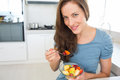 Smiling young woman eating fruit salad in kitchen portrait of a the at home Royalty Free Stock Images