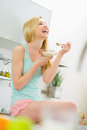 Smiling young woman eating muesli in kitchen Royalty Free Stock Photo