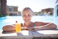 Smiling young woman enjoying a drink in the pool refreshing orange or cocktail resting her arms on surround at Royalty Free Stock Photography