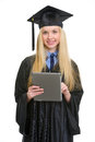 Smiling young woman in graduation gown using tablet pc isolated on white Royalty Free Stock Image