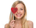 Smiling young woman with heart shaped lollipop isolated on white Stock Photography