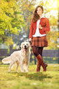 Smiling young woman with her dog in a park labrador retreiver Royalty Free Stock Photography