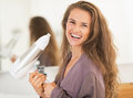 Smiling young woman holding blow dryer in bathroom Royalty Free Stock Image