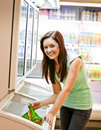 Smiling young woman holding a deep-frozen product Royalty Free Stock Images
