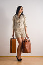 Smiling young woman holding her suitcases and waiting to go on a trip Royalty Free Stock Photos