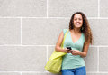 Smiling young woman holding mobile phone and bag Royalty Free Stock Photo