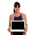 Smiling young woman holding and showing her laptop Stock Photo