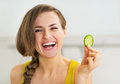 Smiling young woman holding slice of cucumber Royalty Free Stock Photo