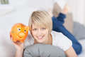 Smiling young woman holding up a piggy bank as she relaxes on her stomach on sofa showing responsible attitude towards saving Royalty Free Stock Photos