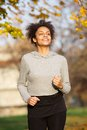 Smiling young woman jogging outdoors in the park Royalty Free Stock Photo