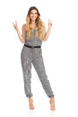 Smiling Young Woman In Jumpsuit Is Showing Peace Hand Sign Royalty Free Stock Photo