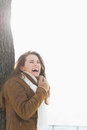 Smiling young woman leaning against tree in winter park with long hair Stock Image