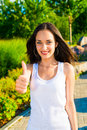 Smiling young woman lifts thumb remarkable in white blouse as a sign of approval on green background of city park Stock Photo