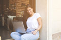 Smiling young woman is looking at you while working on net-book in contemporary coffee shop. Royalty Free Stock Photo
