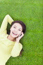 Smiling young woman lying with cell phone on green meadow in park Stock Photo