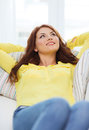 Smiling young woman lying on sofa at home and happiness concept Stock Photos
