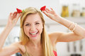 Smiling young woman making horns with strawberries in modern kitchen Royalty Free Stock Image
