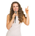 Smiling young woman with microphone pointing up