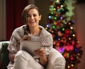 Smiling young woman near christmas tree using tablet pc high resolution photo Royalty Free Stock Photo