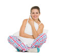 Smiling young woman in pajamas sitting with pillow Royalty Free Stock Photography