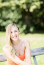 Smiling young woman on a park bench with long blond hair sitting wooden relaxing hot summer day Royalty Free Stock Images