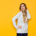 Smiling Young Woman In Pastel Sweater Is Looking Over Shoulder And Smiling Royalty Free Stock Photo