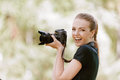Smiling young woman photographs on Stock Photography