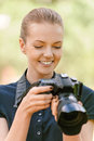 Smiling young woman photographs on camera beautiful in dark blouse against green of summer park Stock Photos