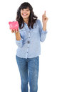 Smiling young woman with piggy bank pointing her finger on white background Royalty Free Stock Photos