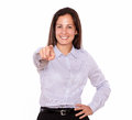 Smiling young woman pointing while standing portrait of a at you on white background Stock Photo