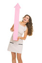 Smiling young woman pointing up on copy space full length portrait of with arrow Stock Image