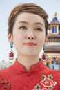 Smiling young woman with qipao chinese building in background Royalty Free Stock Images