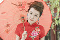 Smiling young woman in qipao holding umbrella and looking at camera Stock Photos