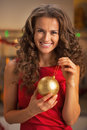 Smiling young woman in red dress holding christmas ball kitchen Stock Image